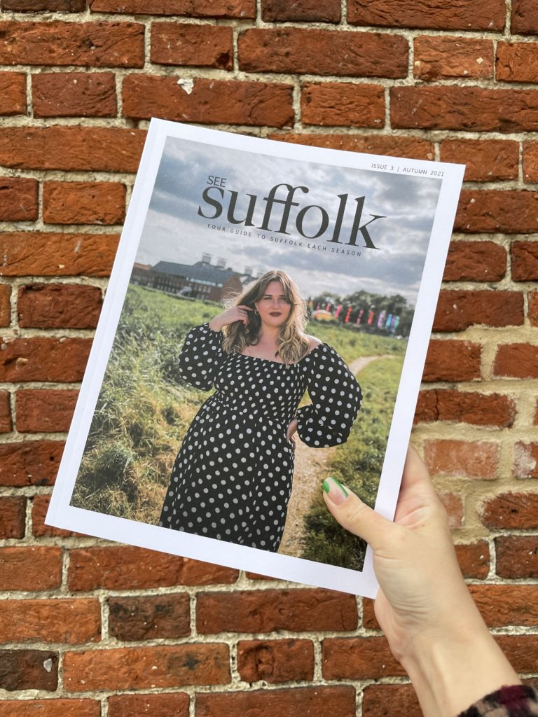 See Suffolk Autumn magazine being held up in front of a brick wall